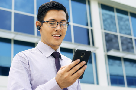 video conference: Young chinese businessman doing video conference call on smartphone and talking with bluetooth headset device in the street Stock Photo
