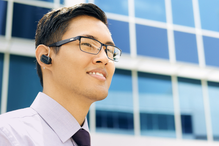 handsfree phones: Portrait of confident asian businessman. The man stands in a street against office buildings and looks away with bluetooth headset. Copy space