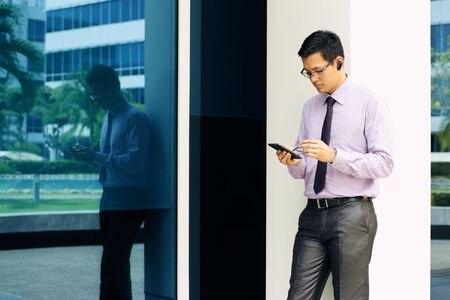 mobile headset: Young chinese businessman typing note on mobile phone while calling with bluetooth headset device. The man uses a digital pen to write on phablet Stock Photo