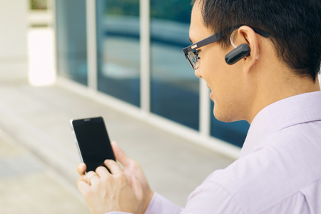 bluetooth: Young chinese businessman typing phone number on smartphone and talking with bluetooth headset device
