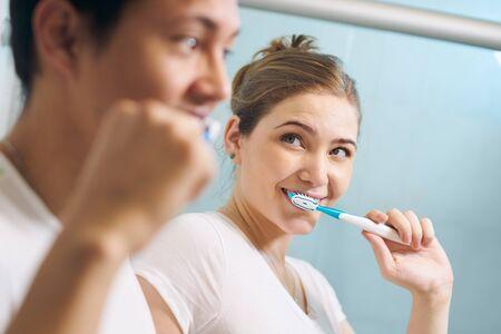 familias unidas: Pareja joven viviendo juntas, lavando los dientes en el baño de la mañana. La mujer se ve feliz en su novio. Concepto de nueva relación y comienzos