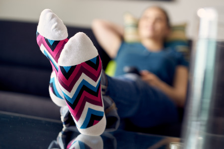 Young caucasian woman laying on sofa with colourful socks. She puts her feet on table and relaxes. The girl watches TV and holds remote control. Focus on socks 免版税图像