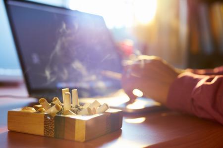 灰皿のタバコの完全なラップトップ コンピューターで作業して、早朝の屋内での喫煙はバック グラウンドで人をクローズ アップ。中毒やニコチン