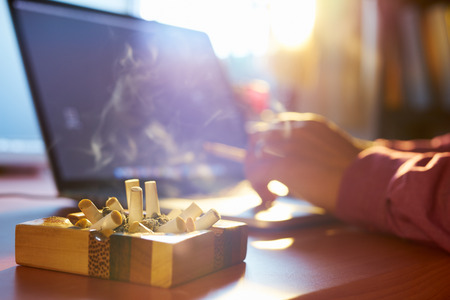 Close up of ashtray full of cigarette, with man in background working on laptop computer and smoking indoors on early morning. Concept of addiction and abuse of nicotine. Banque d'images