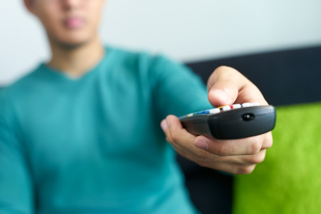 Asian young adult man watching TV and changing channel with remote control. Narrow focus on buttons and hand in foreground, cropped view.