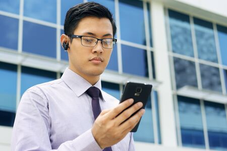 bluetooth: Young chinese businessman doing video conference call on smartphone and talking with bluetooth headset device in the street, looking at screen