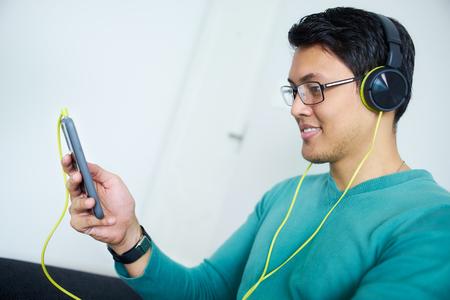 escuchando musica: Hombre chino se relaja en el sofá y relojes de podcast en el teléfono móvil, escuchando con verdes grandes auriculares. Copia espacio Foto de archivo