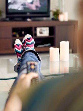 Young caucasian woman laying on sofa with colourful socks. She puts her feet on table and relaxes. The girl watches TV and holds remote control. Focus on socks Stockfoto