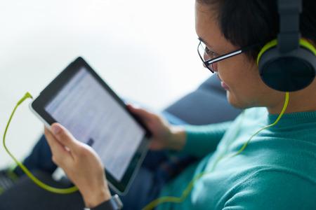 escuchando musica: Hombre chino se relaja en el sofá y relojes de podcast en el PC tableta, escuchando con verdes grandes auriculares. Copia espacio