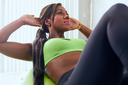 abdominals: Young adult african american woman in sports clothing at home, doing domestic fitness and training abdominals on swiss ball
