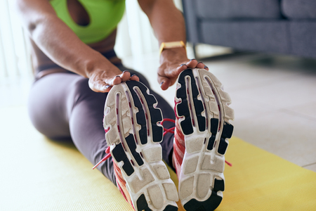 Young adult african american woman in sports clothing at home, doing domestic fitness and training on yellow pad. The girl does muscular legs stretching touching feet with hands
