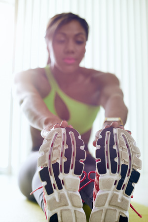 girl working out: Young adult african american woman in sports clothing at home, doing domestic fitness and training on yellow pad. The girl does muscular legs stretching touching feet with hands