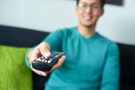 ver television: Asia hombre adulto joven viendo la televisi�n y cambiar de canal con el mando a distancia. Enfoque estrecho en los botones y la mano en primer plano