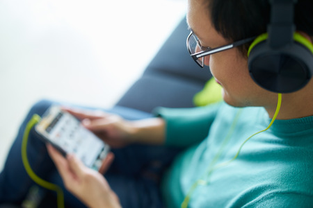 Chinese man relaxes on sofa and watches podcast on mobile phone, listening with green big earphones. Copy space
