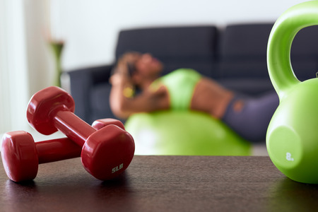 Young adult african american woman in sports clothing at home, doing domestic fitness and training abdominals on swiss ball in living room. Focus on weights on table