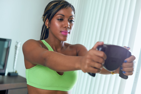 fat and slim: Young adult african american woman in sports clothing measuring body fat with electronic tool. The girl holds the sensors with her hands and looks at the display