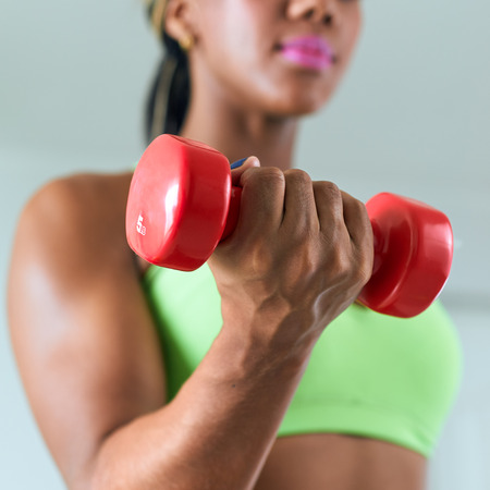 foreground focus: Young adult african american woman in sports clothing at home, doing domestic fitness and training biceps with weight. Focus on weight in foreground
