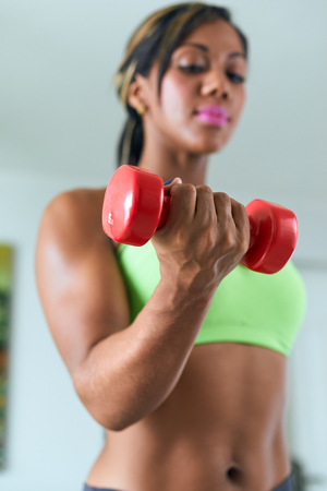 WOMAN FITNESS: Young adult african american woman in sports clothing at home, doing domestic fitness and training biceps with weight. Focus on weight in foreground
