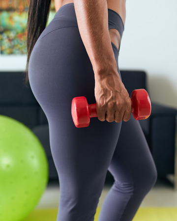 women sport: Young adult african american woman in sports clothing at home, doing domestic fitness and training biceps with weight. Cropped view of hand and legs Stock Photo