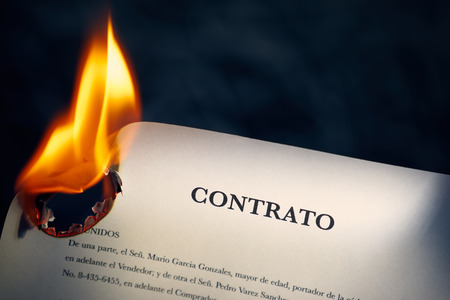new beginnings: Closeup of sale agreement in Spanish burning. Concept shot of freedom and new beginnings