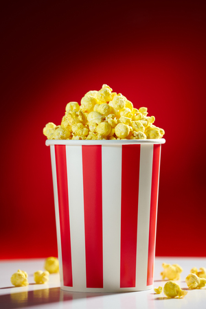 Red bowl full of popcorn on red background for film, TV, television watching. Concept of movie night Archivio Fotografico