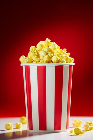 palomitas de maiz: Roja cuenco lleno de palomitas de ma�z en el fondo rojo para cine, TV, ver la televisi�n. Concepto de la noche de pel�cula Foto de archivo
