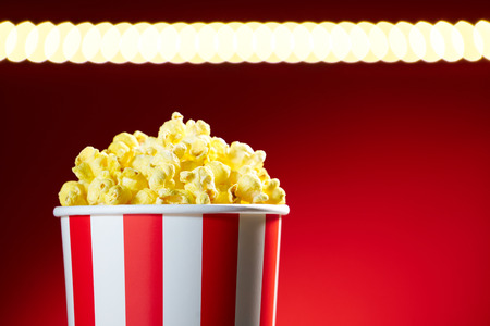 palomitas: Roja cuenco lleno de palomitas de maíz en el fondo rojo para cine, TV, ver la televisión. Concepto de la noche de película Foto de archivo