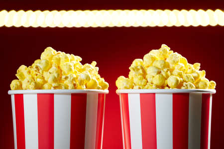 bowl of popcorn: Two red bowls full of popcorns on red background for film, TV, television watching. Concept of couple having a movie night Stock Photo