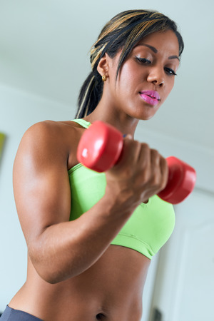 domestic: Young adult african american woman in sports clothing at home, doing domestic fitness and training biceps with weight. Focus on face