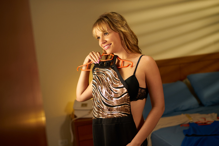 Young attractive woman in lingerie at home, choosing an elegant dress for going out to party at night. The girl looks herself at mirror trying out fashion dress
