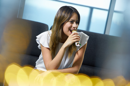 Young hispanic woman at home, relaxing on sofa. The girl eats a tasty cereal bar and smiles