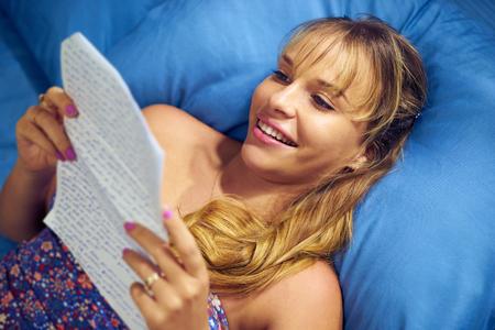 love letter: Joven adolescente caucásicos recibir carta de amor de su nuevo novio. La chica se acuesta en la cama y tiene la letra sonriendo de alegría.