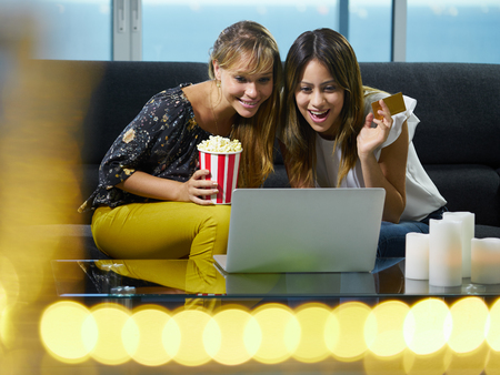 winning bid: Two hispanic female friends sitting on sofa at home, looking at laptop computer and bidding online to buy an item. The girls hold a credit card and smile for joy