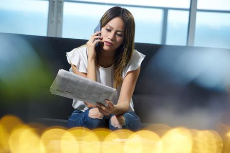 就職と雇用のお知らせを読んで若い失業者の女性。少女新聞を保持彼女のソファに座っているし、面接のための電話をしています。 写真素材