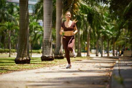 three quarter length: Young blond woman warming up before starting her daily sport routine. The girl does arms stretching in park, near trees. Three quarter length, front view shot Stock Photo
