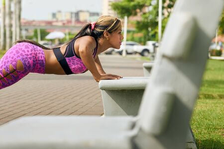 pectorals: Young african american woman training chest and exercising early morning in the city. She trains pectorals on bench along the Cinta Costera in Panama City, doing push ups. Long shot