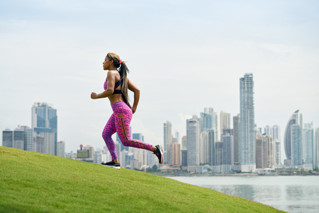 girl in sportswear: Young african american woman running and exercising early morning in the city. She runs on a small hill against the skyline