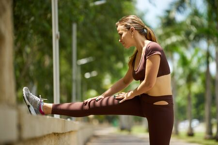 up view: Young blond woman warming up before starting her daily sport routine. The girl does legs stretching in park, near trees. Full length shot