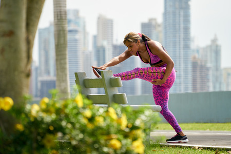 long shot: Young african american woman warming up before starting her daily sport routine. The girl trains at early morning along the Cinta Costera in Panama. Long shot