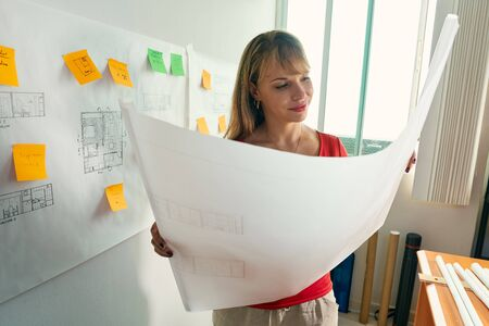 contemplates: University student of Interior Design doing homeworks, reviewing housing project and completing project. The girl contemplates her blueprint and smiles. Stock Photo