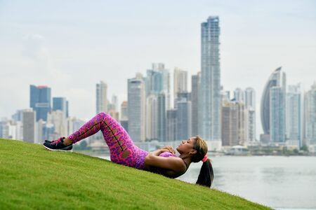 abdominals: Young african american woman training abdominals and exercising early morning in the city. She trains on grass along the Cinta Costera in Panama City. Long shot