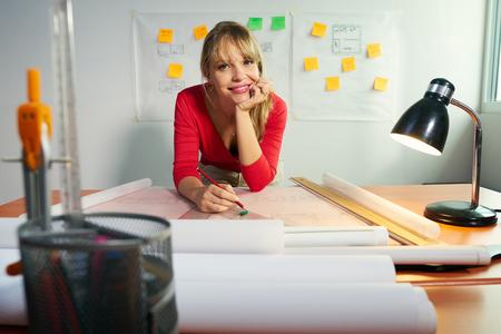 deberes: Estudiante de la Universidad de Diseño de Interiores haciendo tareas, revisión de proyecto de vivienda y completar los proyectos. La chica contempla su plan y sonríe a la cámara Foto de archivo