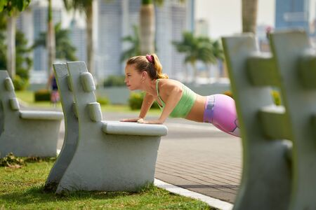 pectorals: Young caucasian woman training chest and exercising early morning in the city. She trains pectorals on bench along the Cinta Costera in Panama City, doing push ups. Long shot