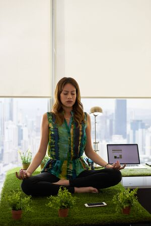 funny people: Young hispanic woman in office, sitting on desk covered with grass and plants. The businesswoman does zen and yoga meditation in lotus position. Full length, front view