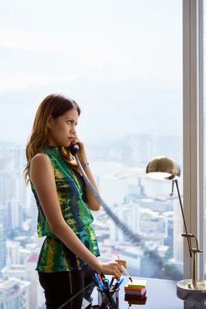 landline phone: Young Hispanic woman leaning on table in a modern office building, with a beautiful sight of the city in background. She holds a wired telephone with long wire and talks looking outside. Copy space Stock Photo