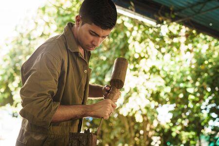 Junger Mann bei der Arbeit Handwerker Beruf zu lernen, die Arbeit mit Hammer und ceasel. Der Künstler schnitzt eine rohe Holzblock eine hölzerne Statue zu machen