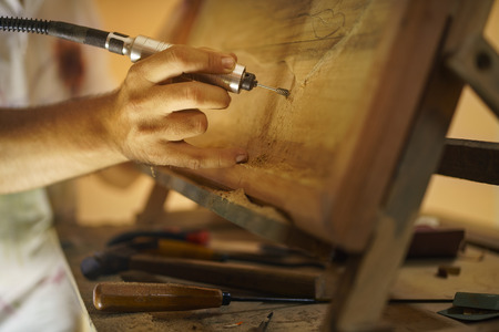 taller: Adult man at work as artist, chiselling a bas-relief in his atelier. He works with a drill to ceasel a wood painting. Stock Photo