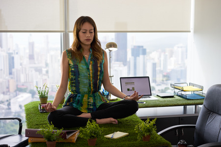 Young hispanic woman in office, sitting on desk covered with grass and plants. The businesswoman does zen and yoga meditation in lotus position. Full length, front view