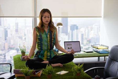 Jonge Spaanse vrouw in kantoor, zittend op het bureau bedekt met gras en planten. De onderneemster doet zen en yoga meditatie in lotushouding. Volledige lengte, vooraanzicht