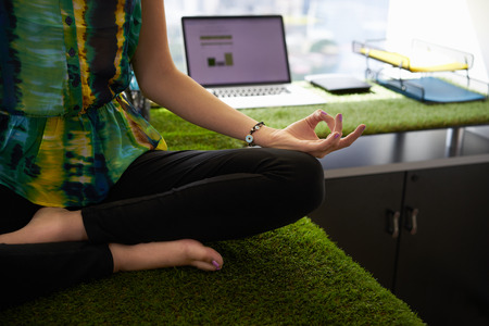 Young hispanic woman in office, sitting on desk covered with grass and plants. She meditates yoga in lotus position. Cropped view of hands and feet Stockfoto